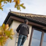 CCTV specialist installing camera on house