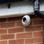 Close up of white security camera underneath black guttering