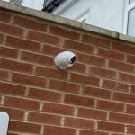 Brick wall with CCTV camera pointing downwards