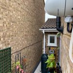 Closeup of white Hikvision CCTV camera on side of house in Royston