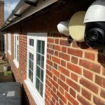 Closeup of 2 security cameras on side of Essex home